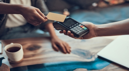 Woman Using Contactless Credit Card with Wireless Payment Terminal Held by Man