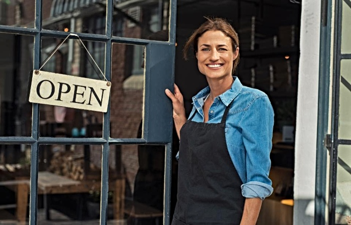 Small Business Owner Stands at Front Door